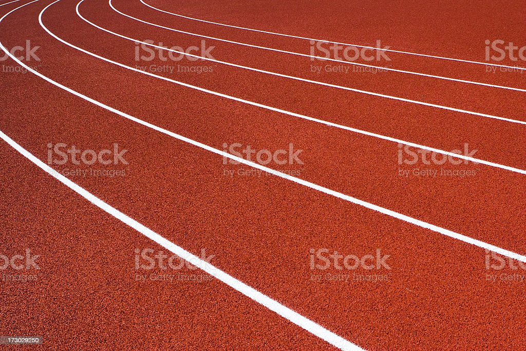 Red orange running track with white lane lines royalty-free stock photo