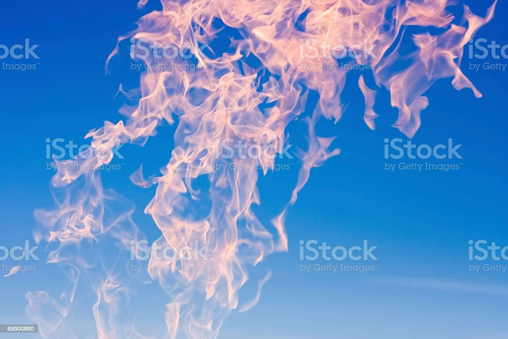 red orange tongues of fire flame on blue sky background stock photo