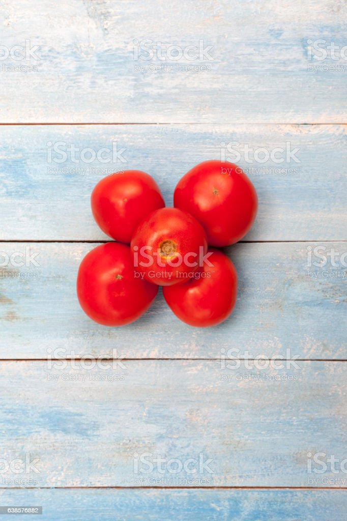 Red organic tomatoes on a blue wooden board, top view stock photo