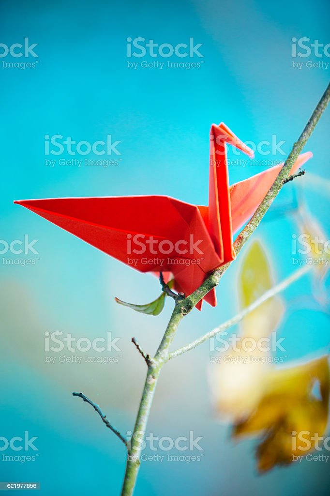 Red origami crane on a tree branch stock photo
