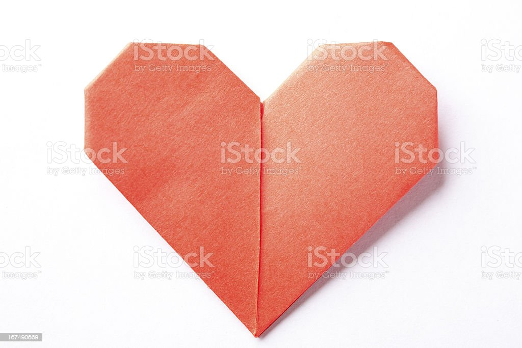 A red origami heart on a white background stock photo