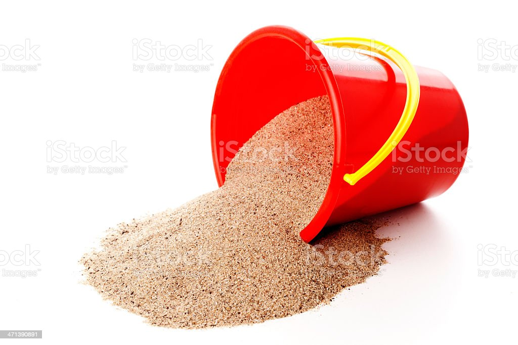 Red pail pouring sand onto white surface stock photo