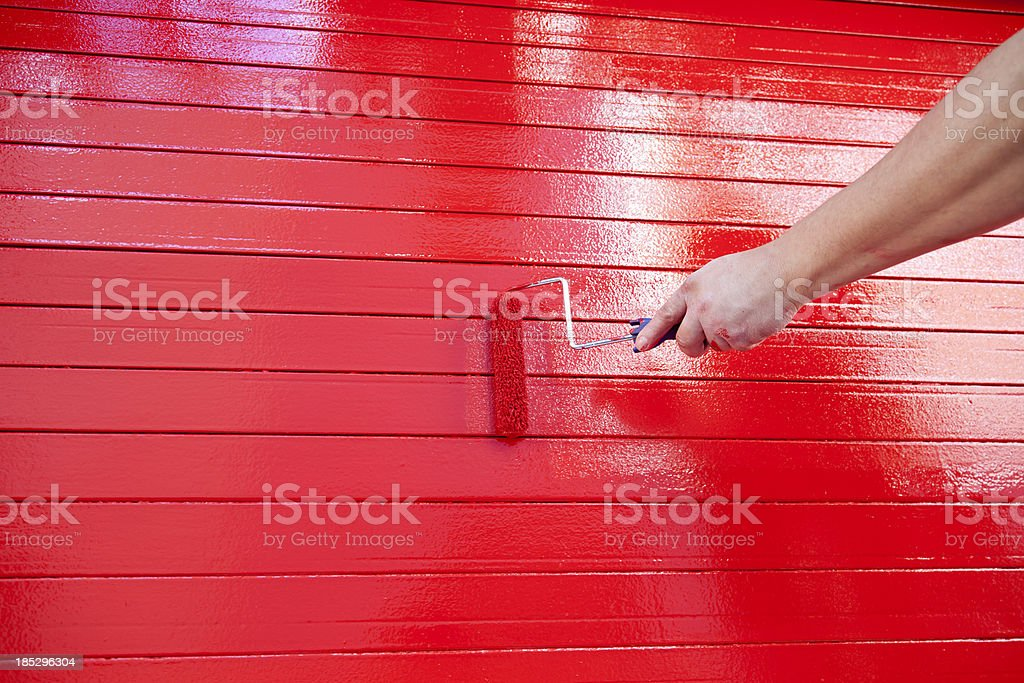 Red Paint: Hand Holding Roller stock photo