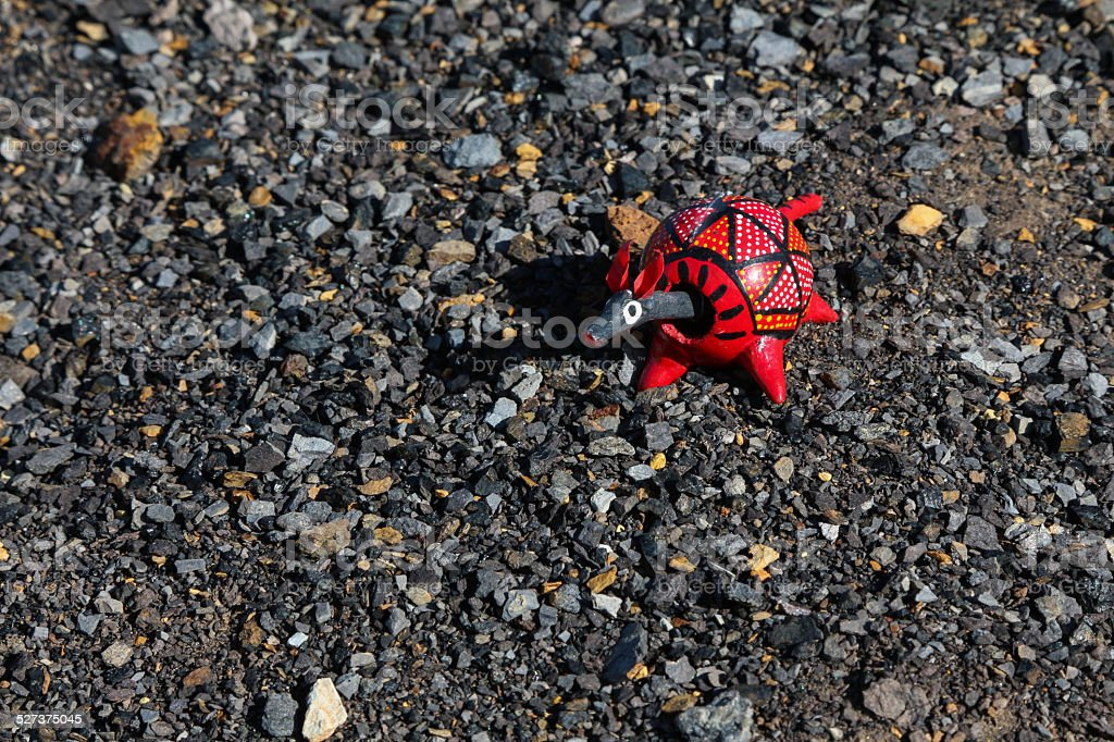 Red painted armadillo bobblehead on black stones stock photo