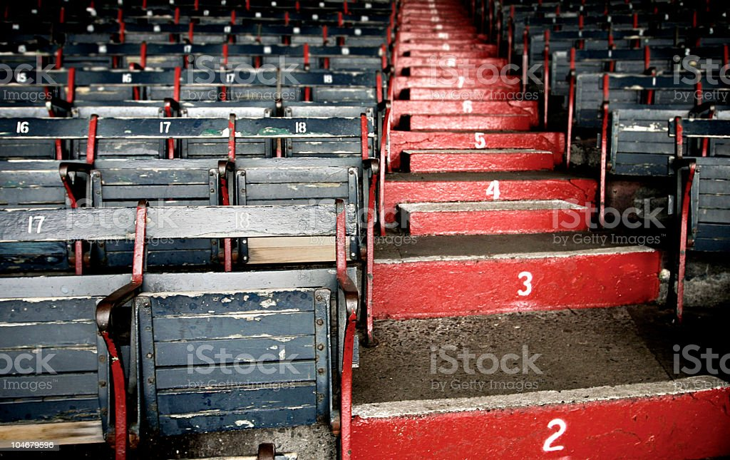 Red painted steps rising between grey stadium seats royalty-free stock photo
