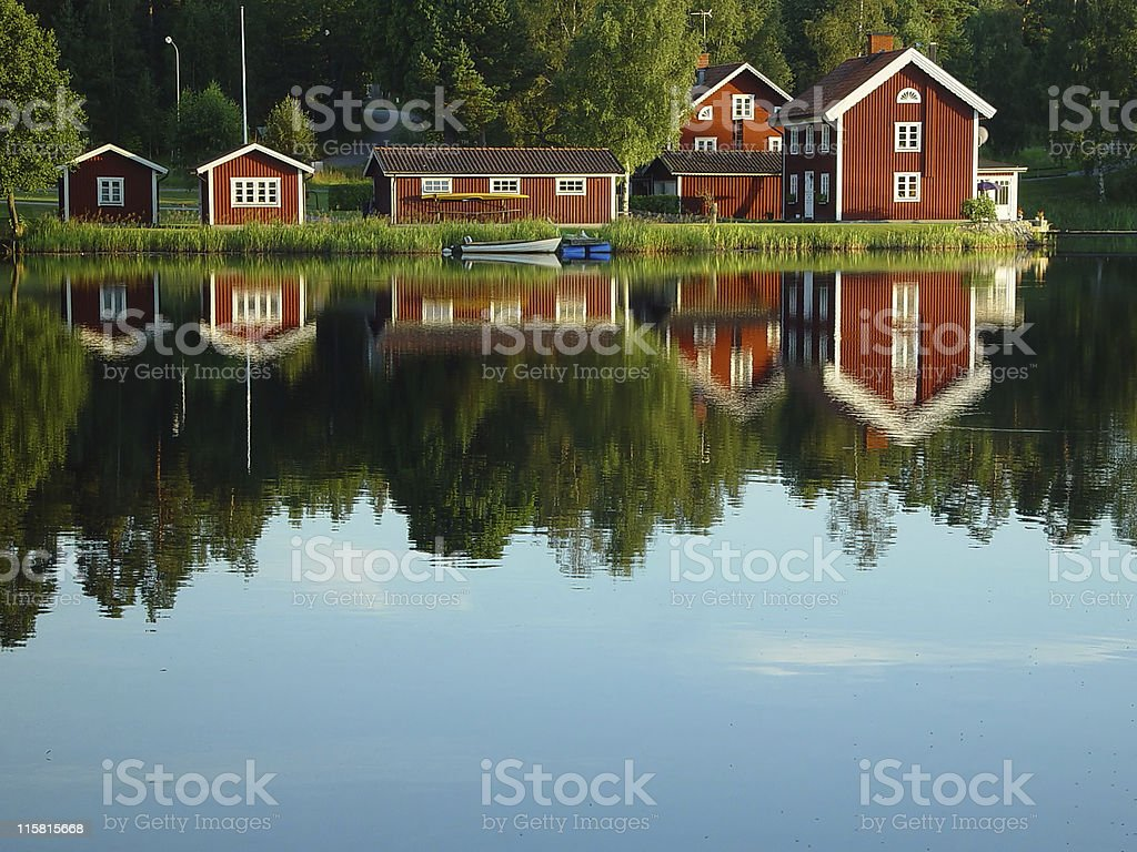 red painted Swedish lakeside houses reflection royalty-free stock photo
