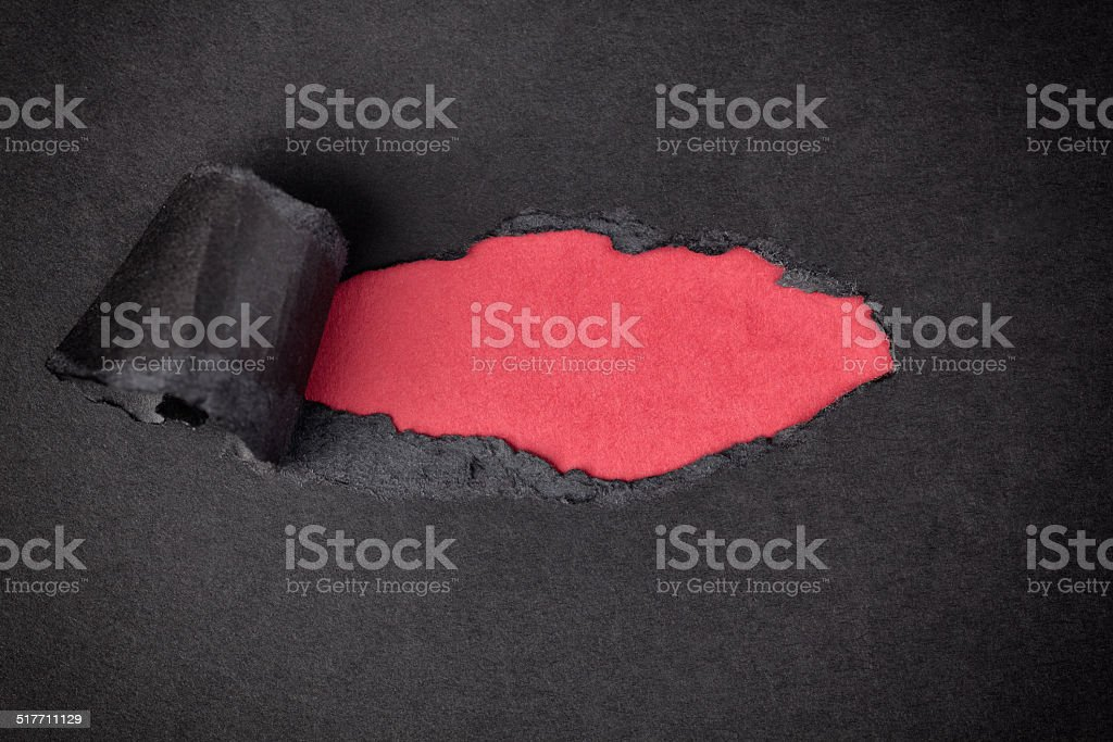 Red paper background appearing behind torn black paper stock photo