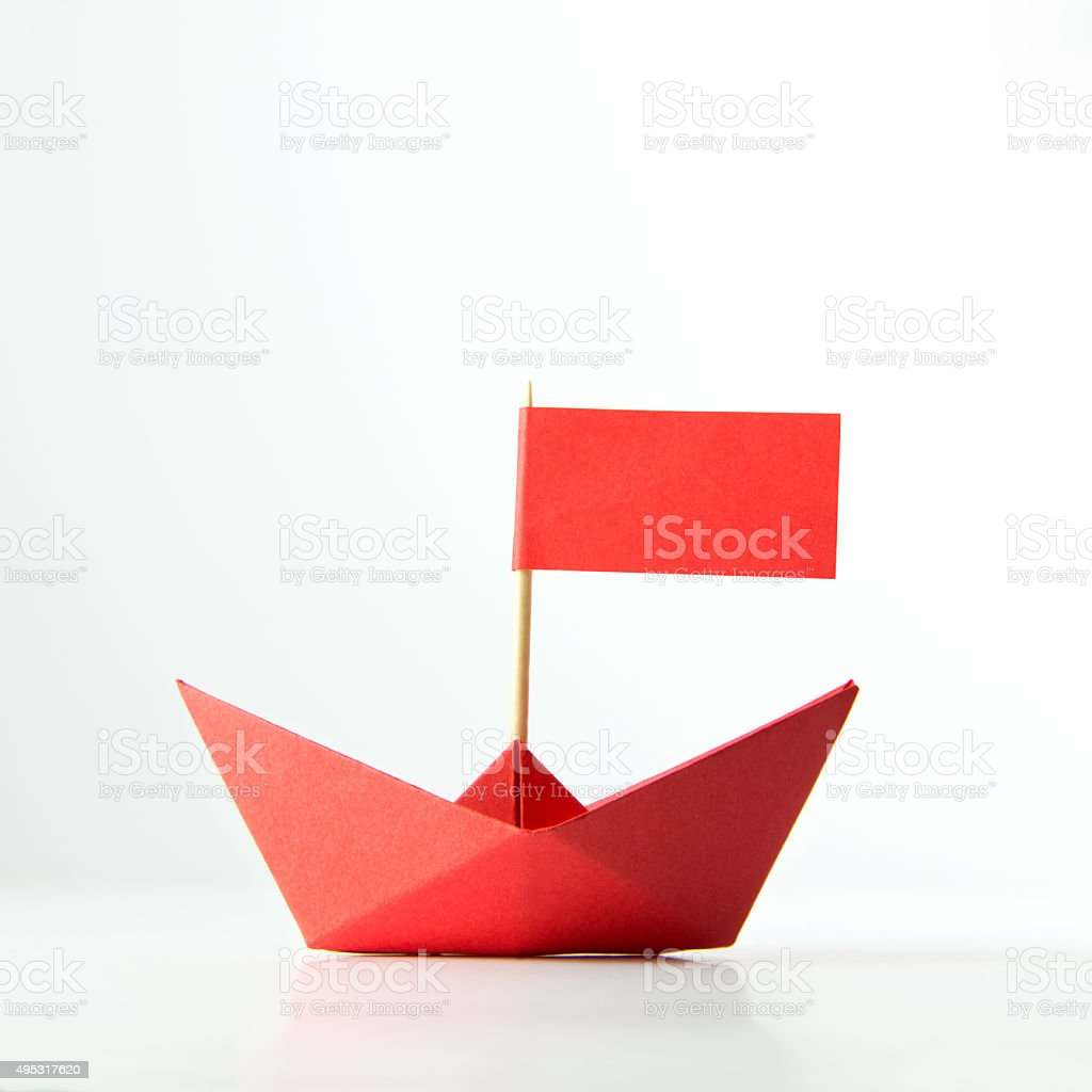 Red paper boat with flag stock photo