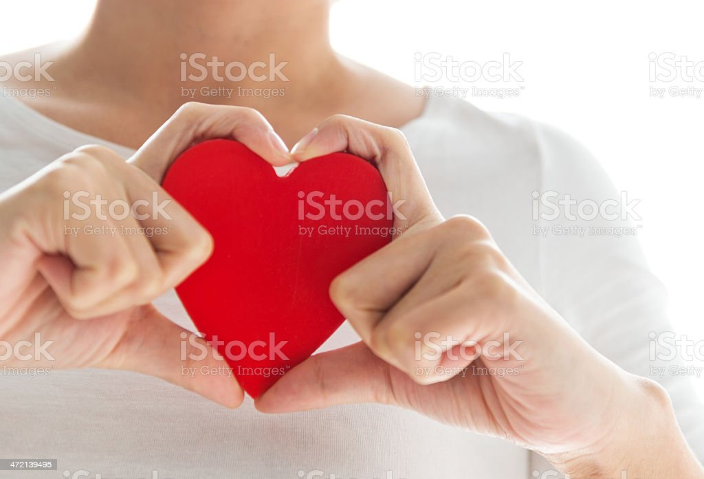 Red paper heart engulfed in fingers shaped like a heart stock photo
