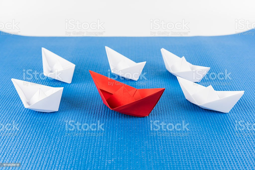 Leadership concept with red paper ship leading among white and blue...