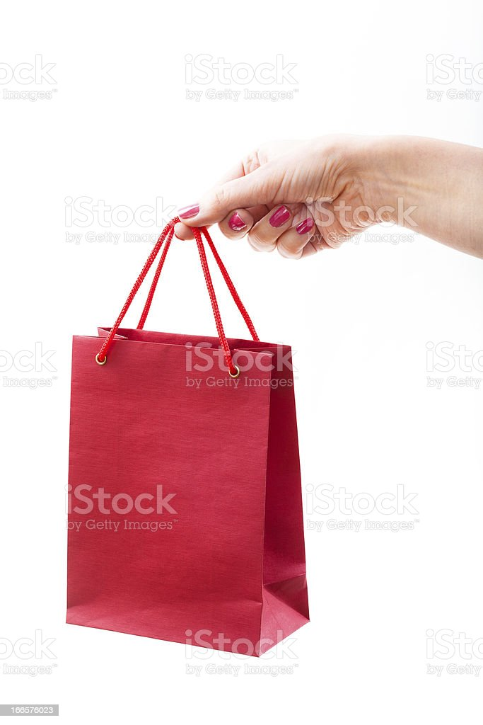 Red paper shopping bag in female hand royalty-free stock photo