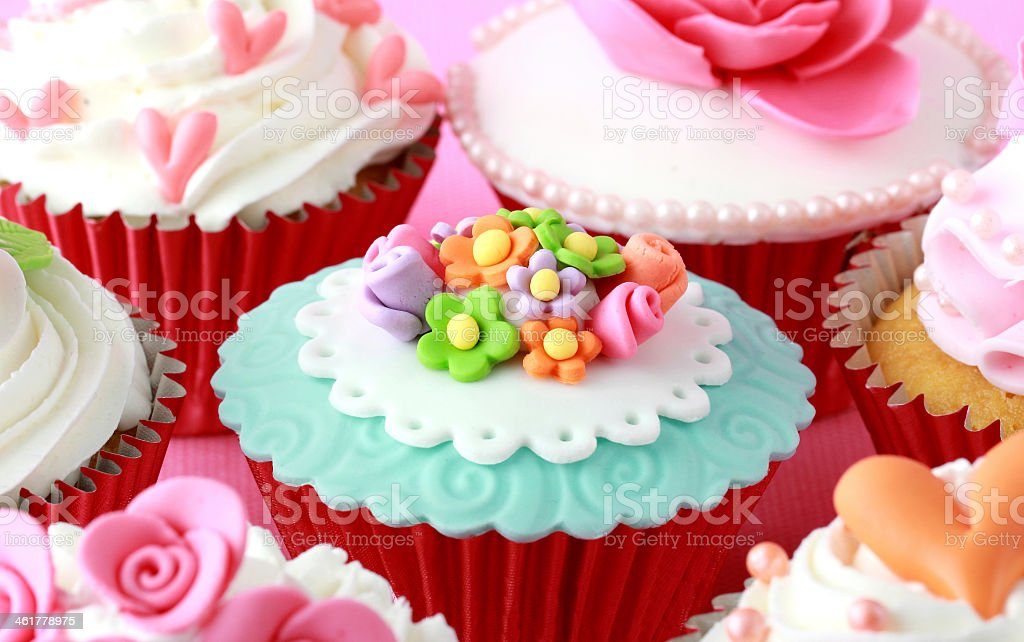 Red papered cupcakes with pastel designs stock photo