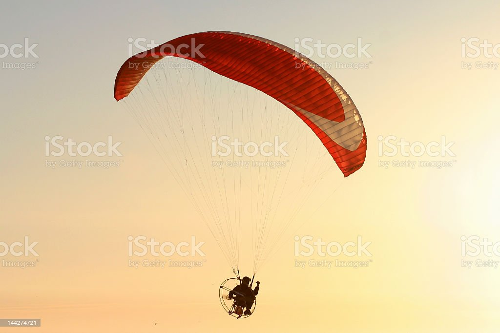 Red parachute flying at sunset stock photo