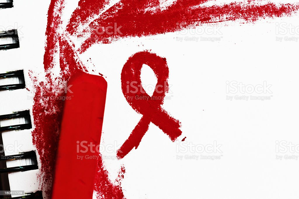 Red pastel  crayon draws the scarlet  AIDS ribbon on sketchpad royalty-free stock photo