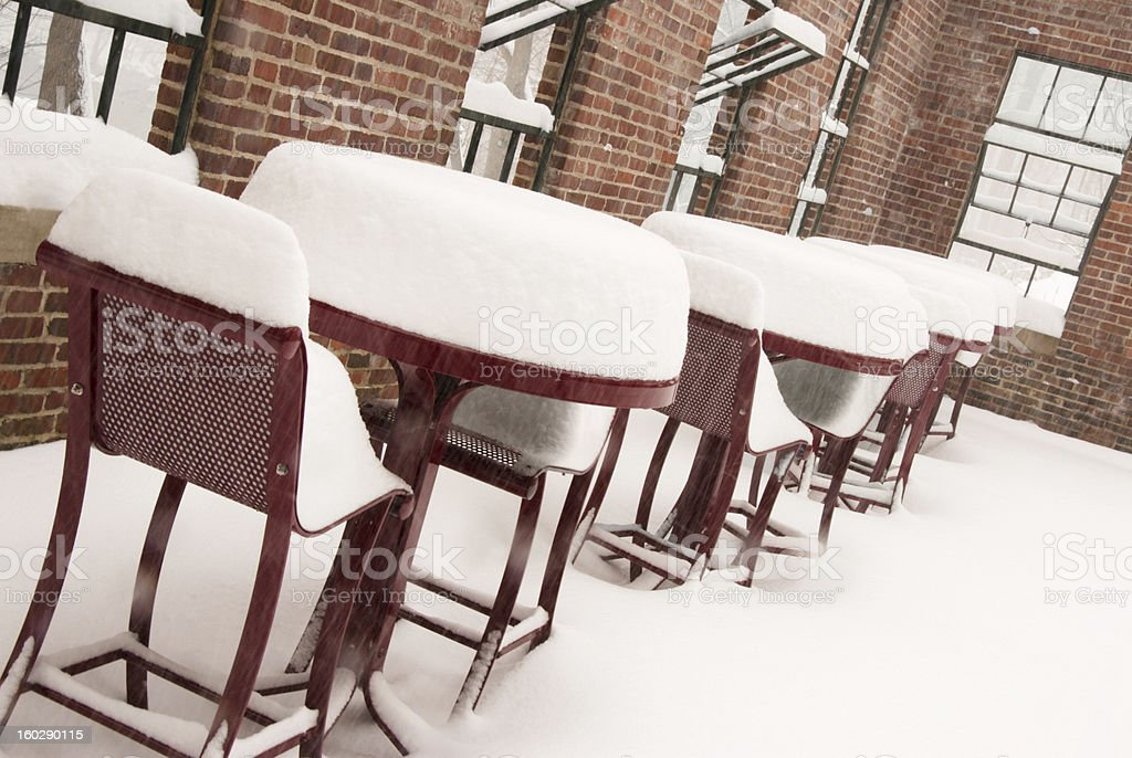red patio furniture covered with snow during blizzard of 2009 stock photo