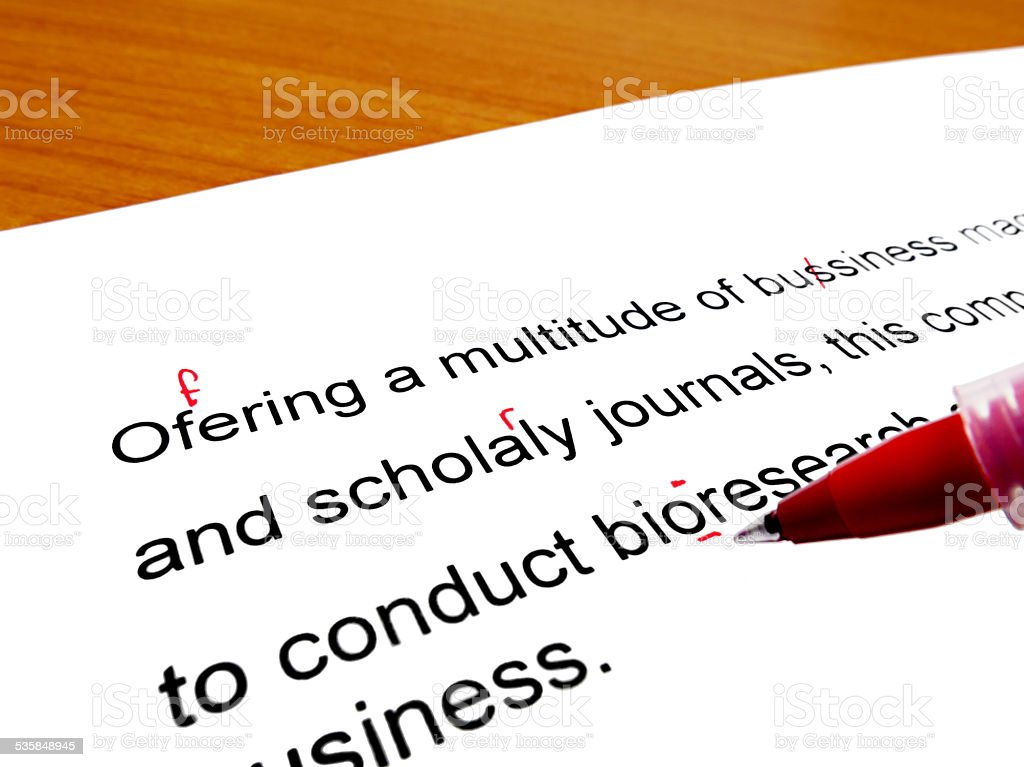 Red pen correcting proofread english text on wooden table stock photo