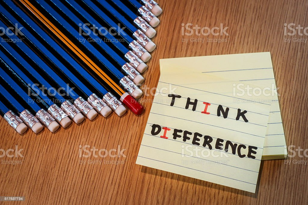 Red pencil standing out from crowd of blue pencils stock photo
