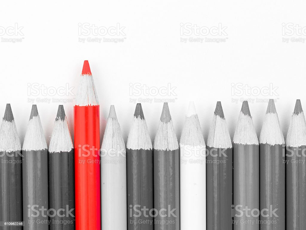 Red pencil standing out from monochrome pencils crowd stock photo