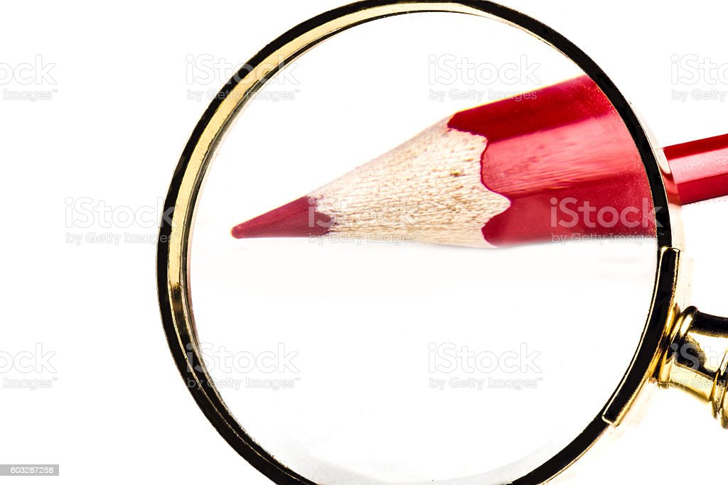 Red pencil through Magnifying glass stock photo