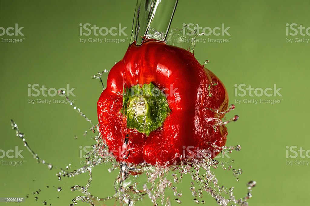 Red pepper and water splash with green background