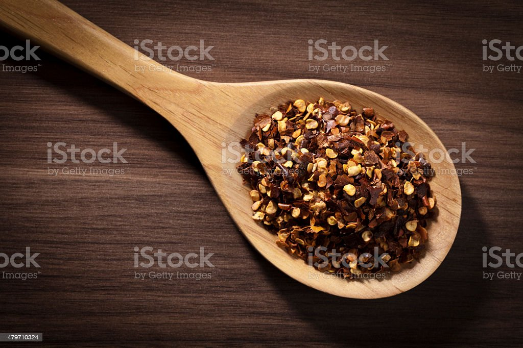 Red pepper flakes in a wooden spoon shot directly above stock photo