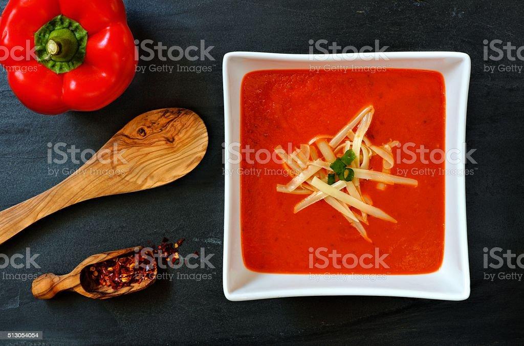 Red pepper soup overhead scene on slate background stock photo