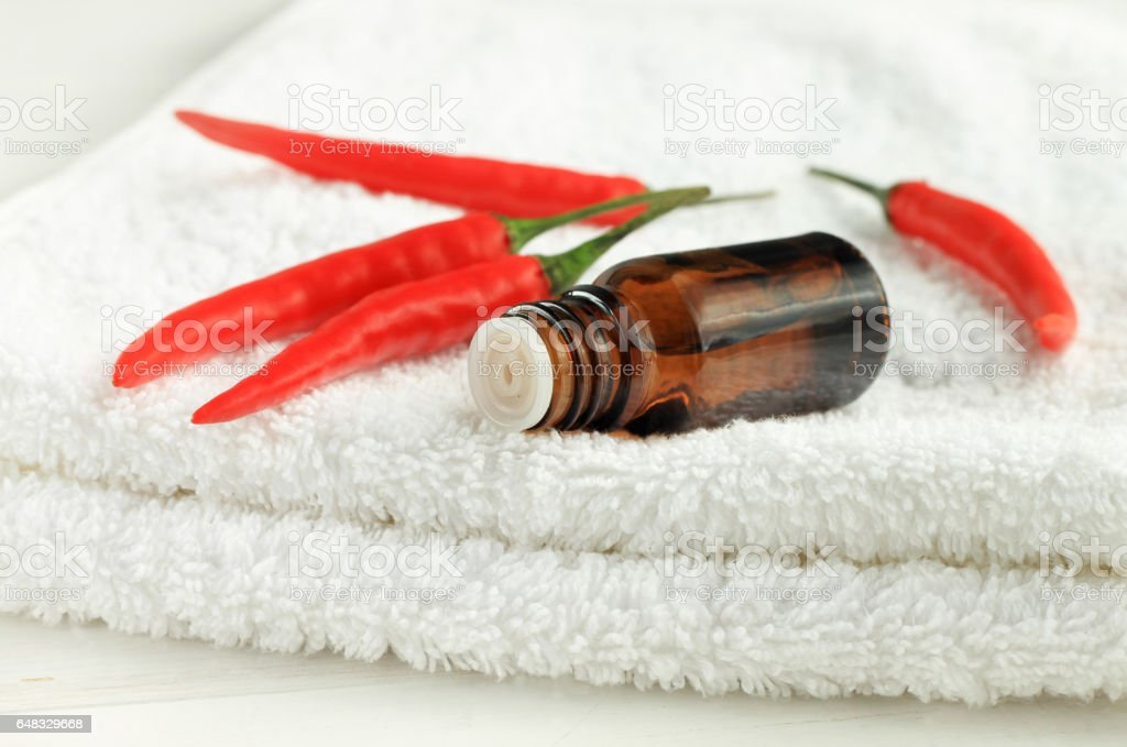 Red pepper tincture in dropper bottle on white towel stock photo