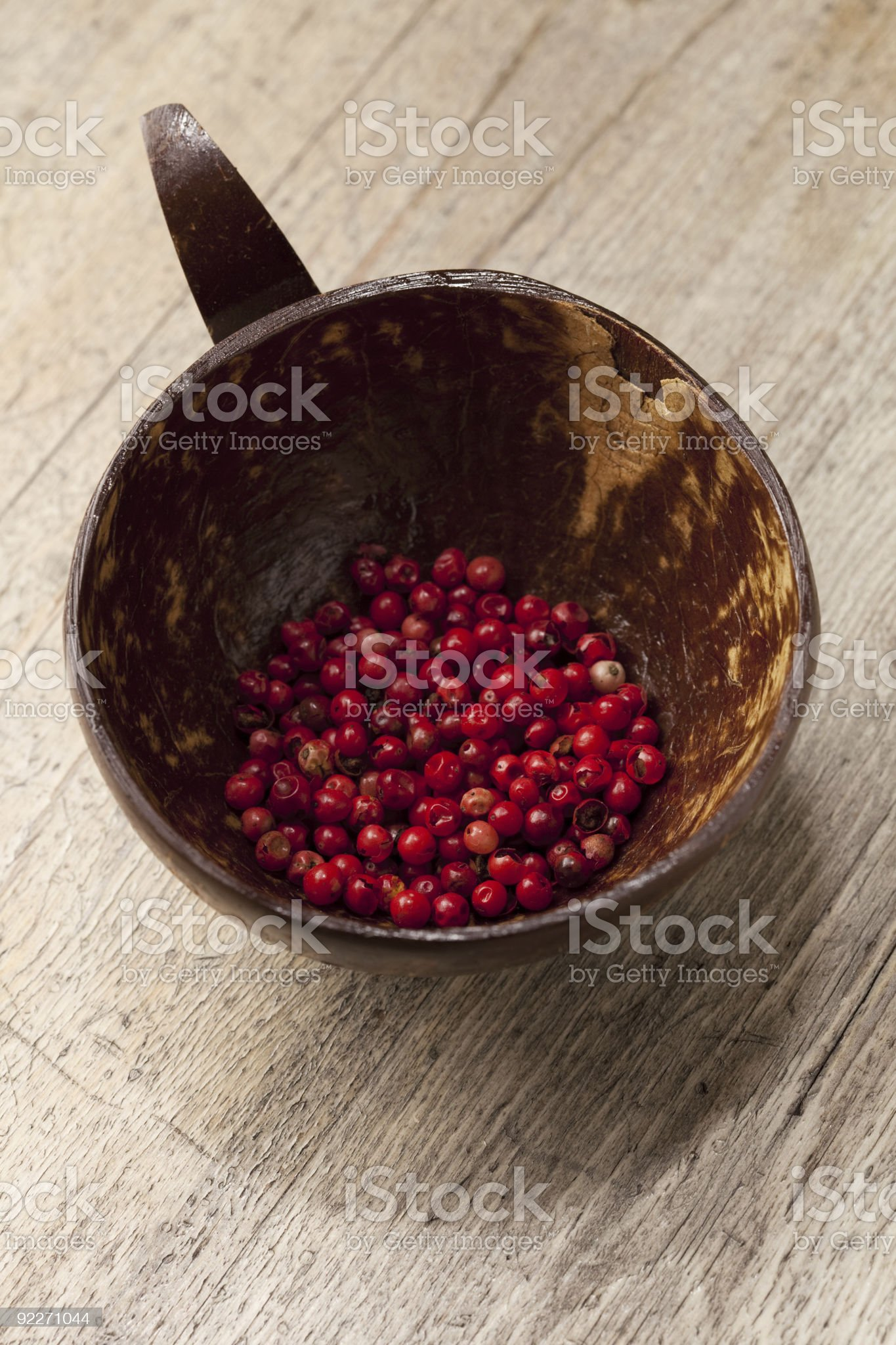 red peppercorn spice in coconut bow on old wooden table royalty-free stock photo