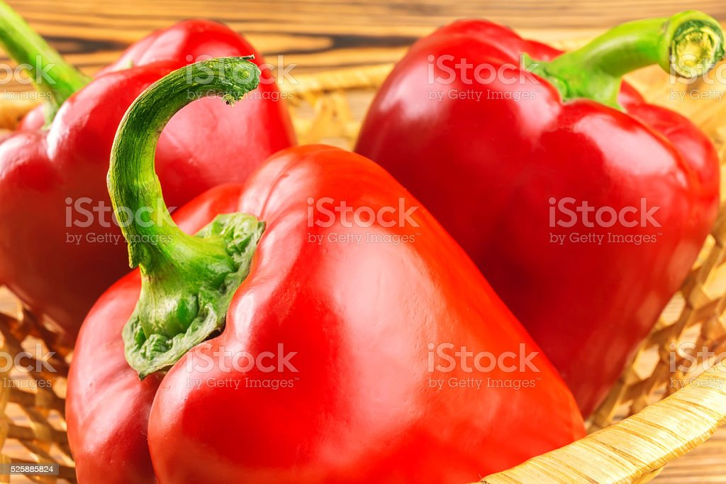 Red peppers in wicker basket, close-up view. stock photo