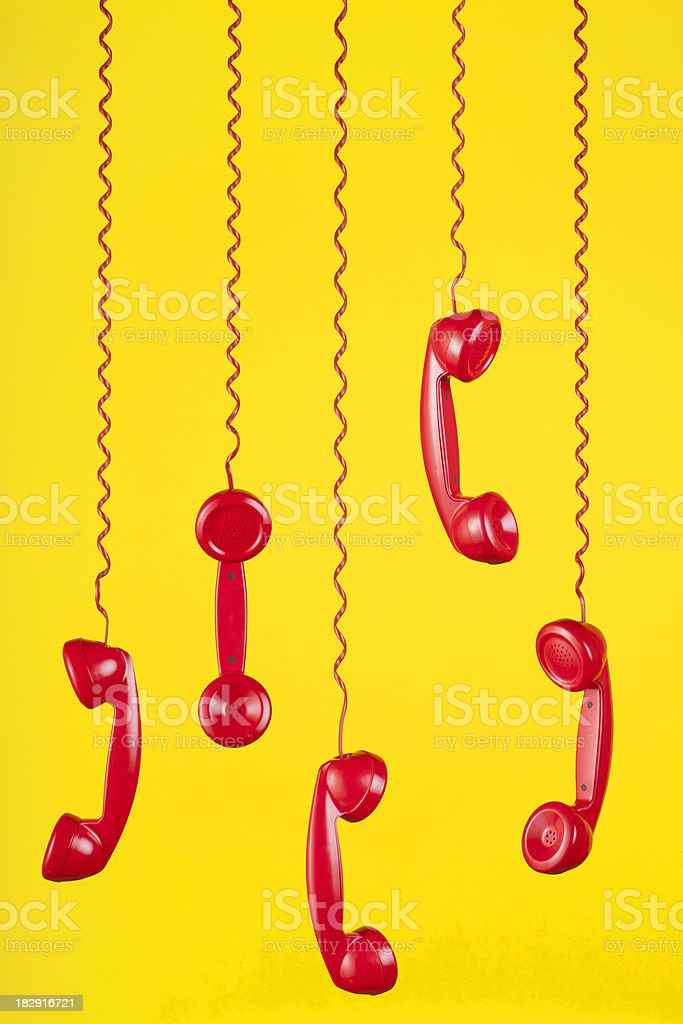 Red Phones Hanging on a Yellow Background stock photo