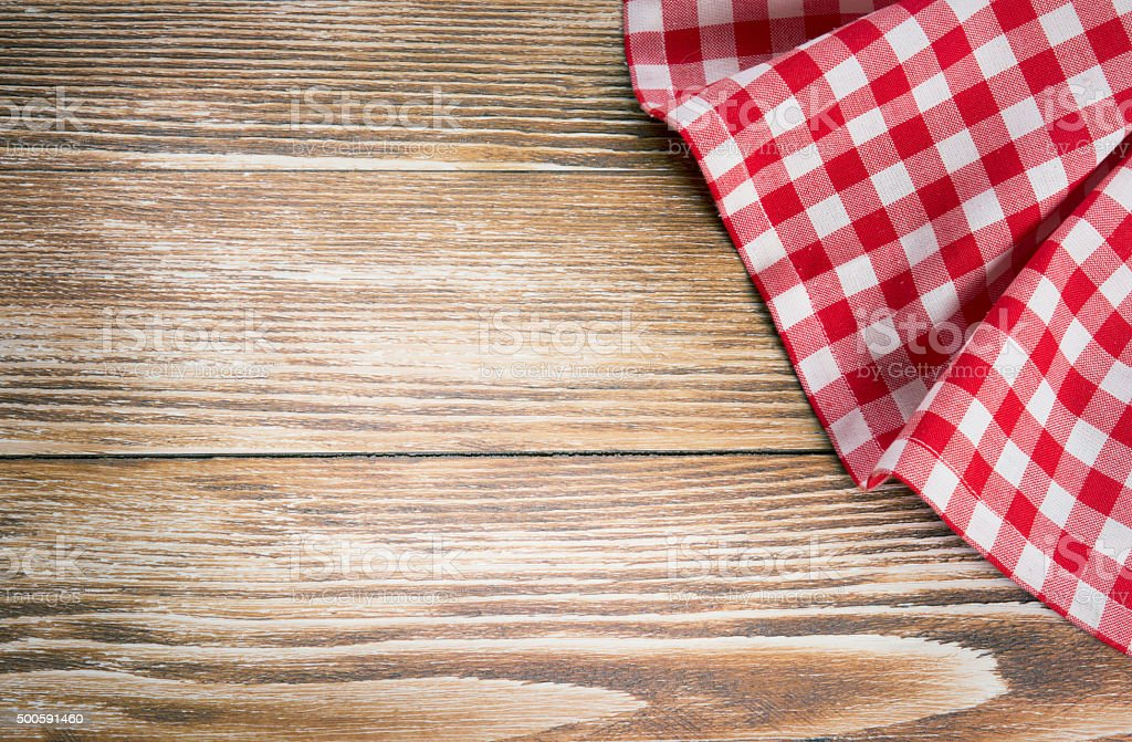 Red picnic cloth on wooden background.Napkin tablecloth on old wood. stock photo