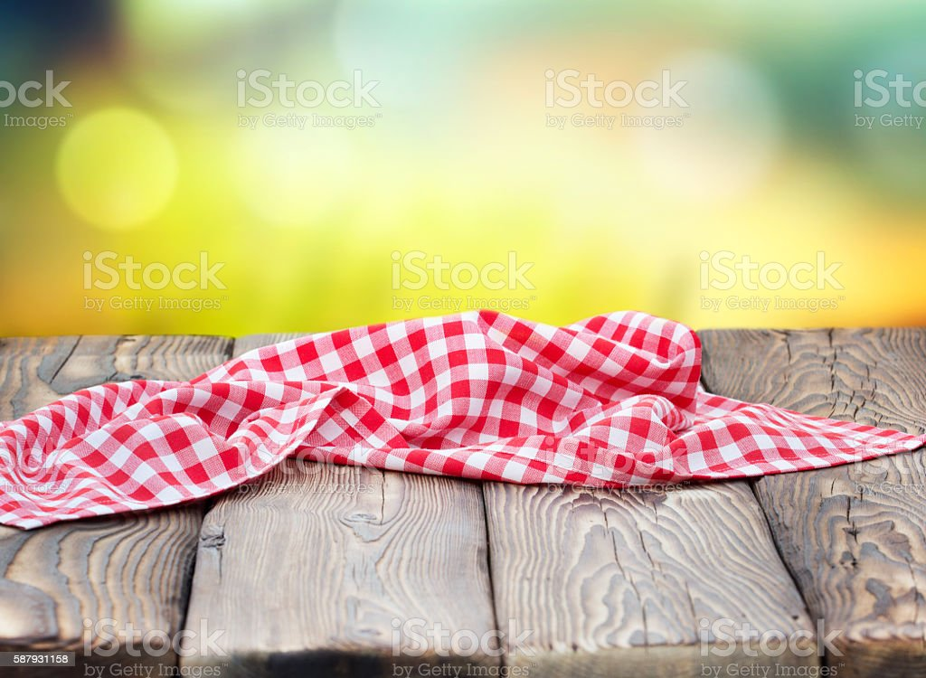 Red picnic cloth on wooden table mature bokeh background. stock photo