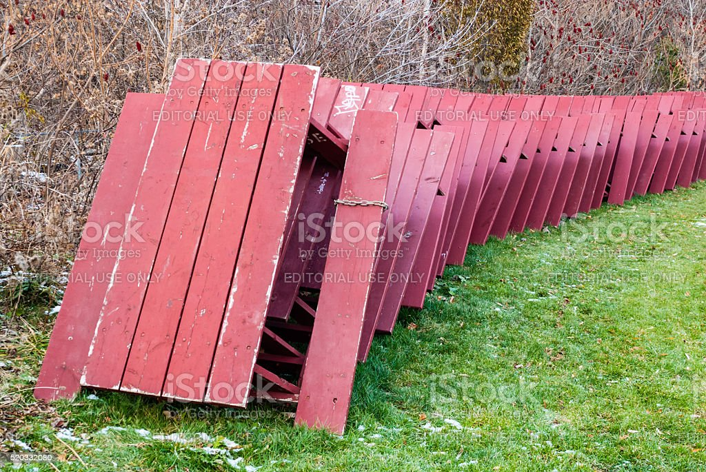 Red picnic tables stacked for winter storage in park. stock photo