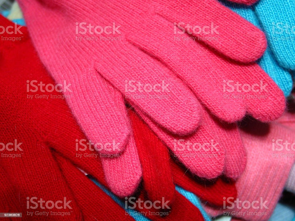 Red, pink and blue warm knitted gloves stock photo