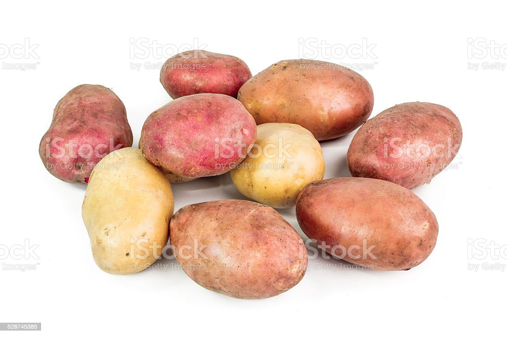 Red, pink and white Potato tubers on white background stock photo