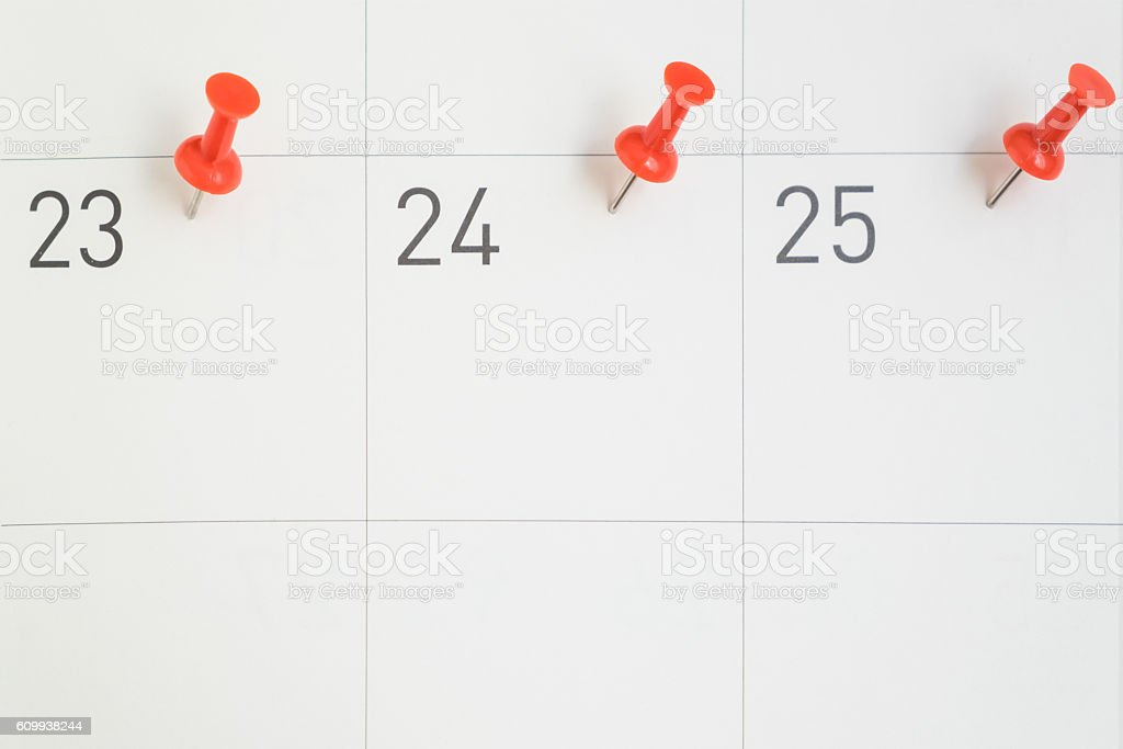 Red pins pinned on dates of month on calendar paper stock photo
