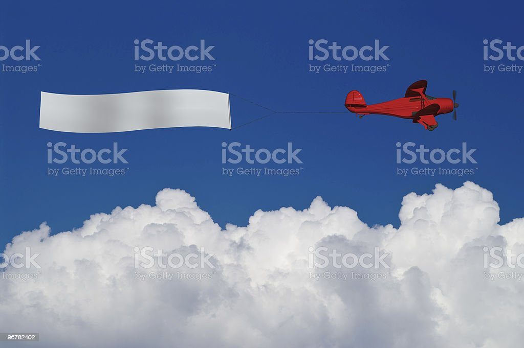 Red plane pulls blank banner above white clouds stock photo