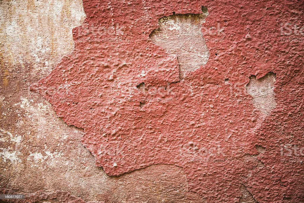 Red plaster partially peeling off of a wall royalty-free stock photo