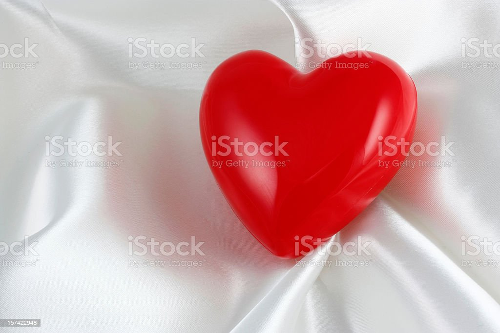 Red Plastic Heart on white satin royalty-free stock photo