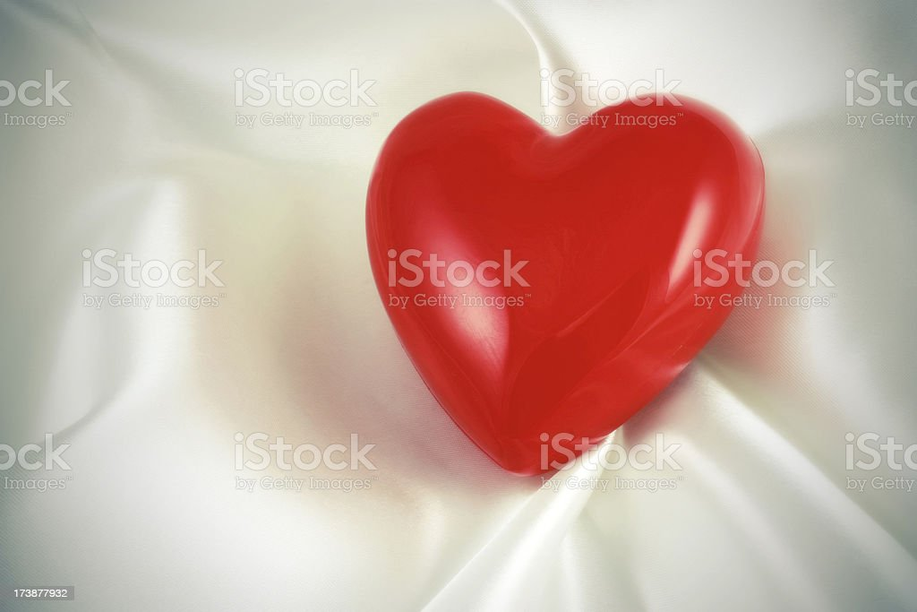 Red Plastic Heart on white satin soft royalty-free stock photo