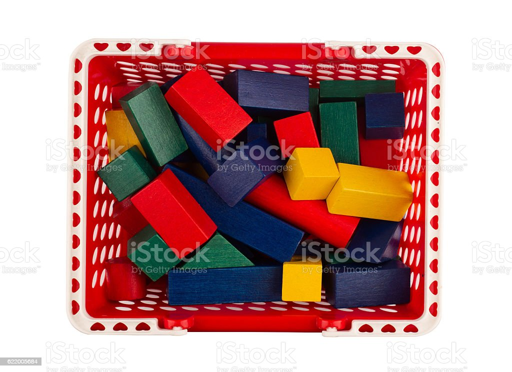 red plastic shopping cart with wooden construction blocks on whi stock photo