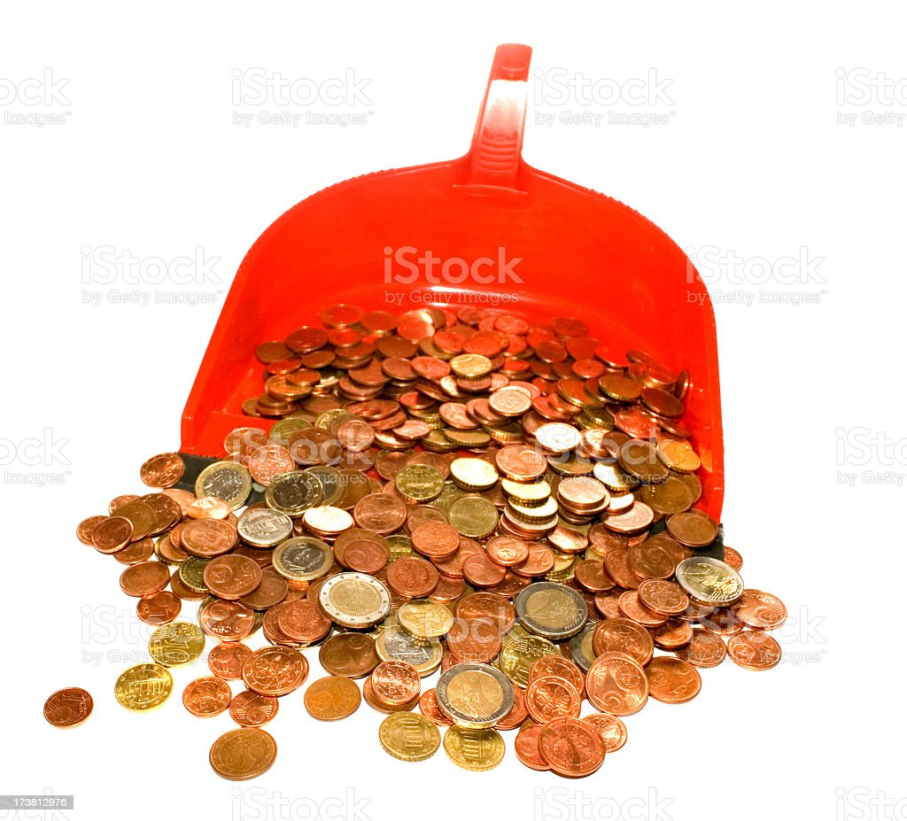 Red plastic shovel full of small change isolated stock photo