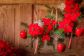 Red poinsettias, candy canes, apples on branch and wood (P)