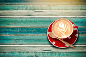 Red polka dot latte cup of coffee top view  plank