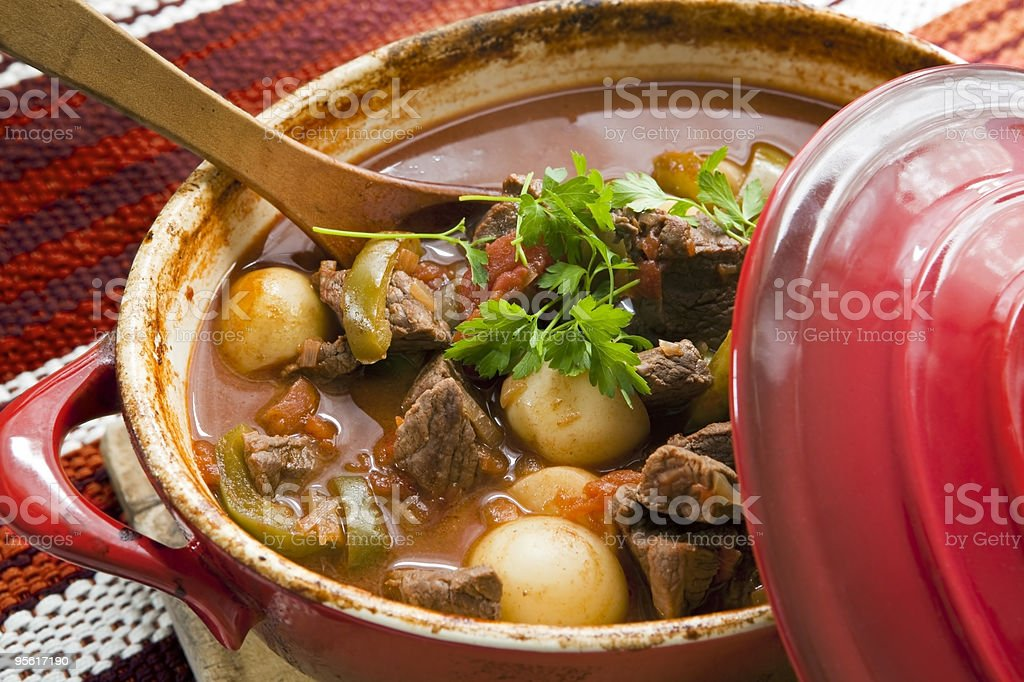 Red pot full of goulash with wooden spoon in it stock photo