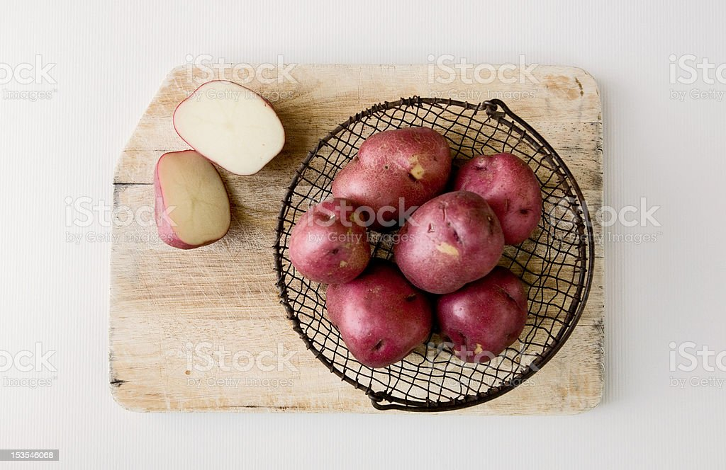 Red potatoes in wire basket on cutting board. stock photo