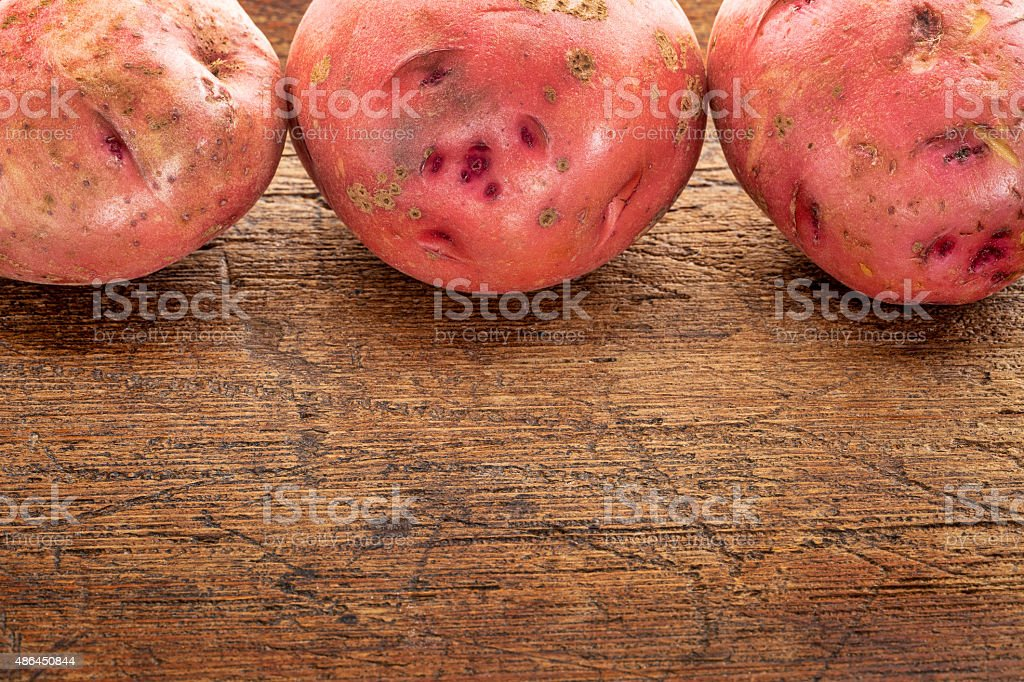 red potatoes on rustic wood stock photo