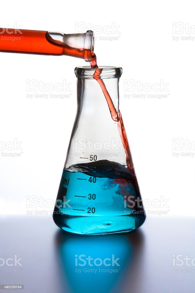 Red pouring liquid in conical flask. stock photo