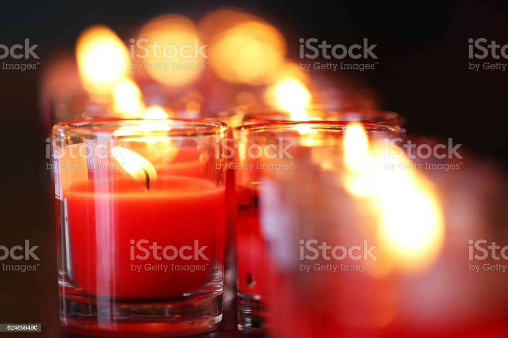 Red prayer candles in small glasses stock photo