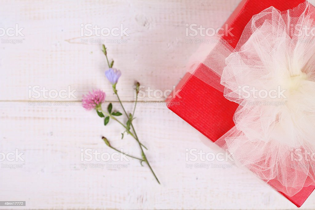 Red present box with white Ribbon on white wooden backgroung stock photo